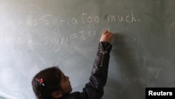 """FILE - A Syrian refugee girl writes """"we miss Syria too much"""" on the chalkboard in her classroom in Majdel Anjar in Bekaa Valley December 27, 2012."""