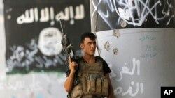 A member of Iraqi counterterrorism forces stands guard near Islamic State militant graffiti in Fallujah, Iraq, June 27, 2016.