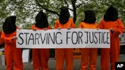 Protesters depicting detainees of the US detention facility at Guantanamo Bay, Cuba, hold a banner, during a demonstration outside the US embassy in central London, May 18, 2013.