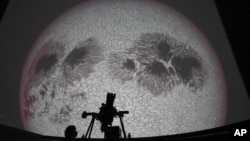 Researcher Ivannia Calvo, silhouetted against a solar satellite image, works inside the Solar Astronomical Observatory in San Jose, Costa Rica, Friday, April 30, 2021. Costa Rica approved a law creating a space agency on Feb. 18. (AP Photo/Carlos Gonzalez