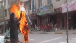 A woman throws a white scarf over Tibetan Buddhist nun Palden Choetso as she burns on the street in Daofu, China - or Tawu in Tibetan - November 3, 2011.