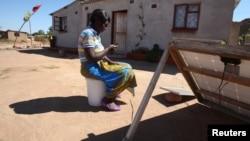 Une femme regarde son téléphone portable à Epworth, à l'est de la capitale Harare, Zimbabwe, le 11 août 2016.