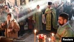 Para pendeta dan umat mengikuti misa di tengah wabah virus corona di Omsk, Rusia, 11 April 2020. (Foto: Reuters)