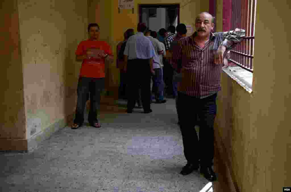 Men wait to vote at a polling station in central Cairo, Egypt, June 16, 2012. (Y. Weeks/VOA)