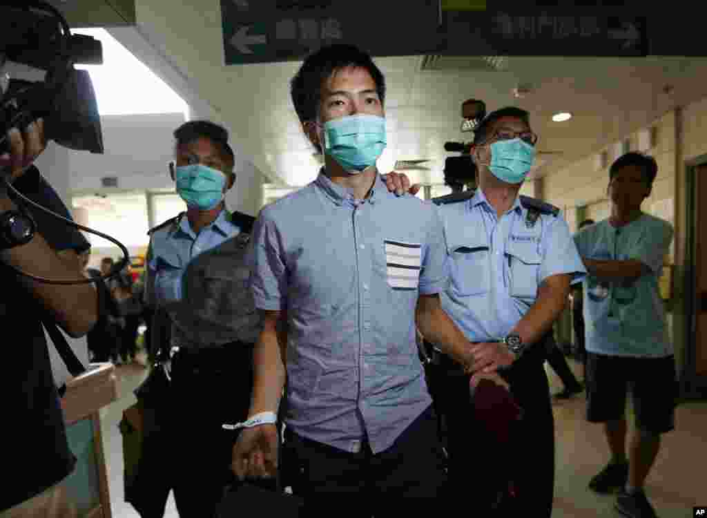 An Occupy Central protester is escorted by police officers to a hospital for injuries sustained during a clash between protesters and police near the government headquarters in Hong Kong, Oct. 15, 2014.