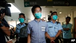 An Occupy Central protester, center, is escorted by police to a hospital for examine his injury during a clash between protesters and police in an occupied area near the government headquarters in Hong Kong, Oct. 15, 2014.