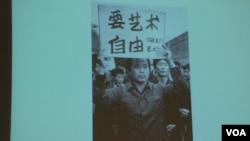 舒陽展示1979年10月北京藝術家參與遊行時高舉「要藝術要自由」的標語的照片