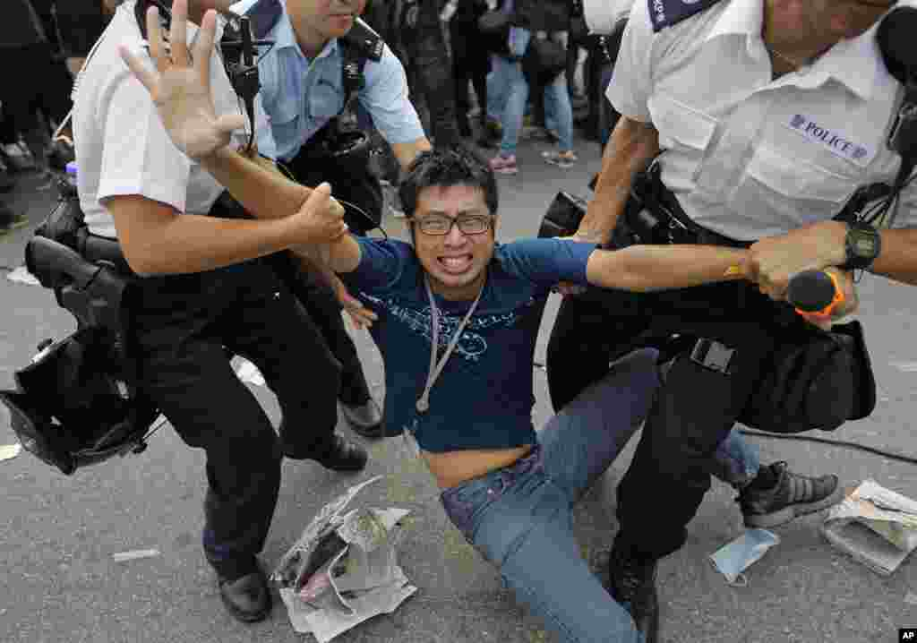 A pro-democracy protester is taken away by police offers as an ambulance tries to leave the compound of the chief executive office in Hong Kong.