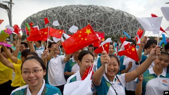 在北京奥林匹克体育场外,人们庆祝北京成功申办2022年冬季奥运会。(2015年7月31日)