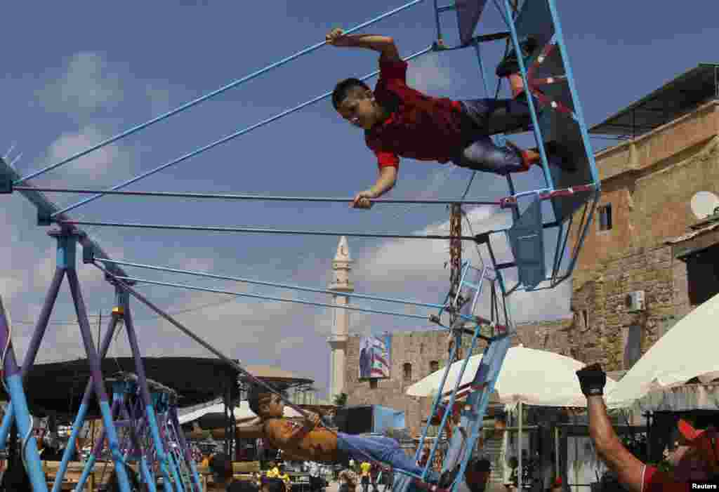 Children ride swings during Eid al-Fitr in the port city of Sidon, southern Lebanon, August 8, 2013.