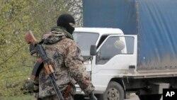 Một tay súng thân Nga canh gác trên con đường sau vụ nổ súng trong đêm tại làng Bulbasika gần Slovyansk, Ukraine, ngày 20/4/2014.