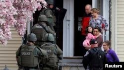 Polisi khusus melakukan pemeriksaan dari rumah ke rumah untuk mencari tersangka Dzhokar Tsarnaev di kota Watertown, Massachusetts, sementara warga diminta keluar rumah mereka (19/4).