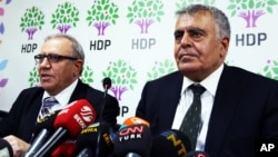 Turkey's Minister for EU Affairs Ali Haydar Konca, left, and Development Minister Muslum Dogan, members of the of the pro-Kurdish People's Democracy Party, or HDP, speak to the media in Ankara, Sept. 22, 2015.