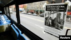 "FILE - A poster entitled ""It All Started On A Bus,"" is pasted above the front seat of a New York City bus to honor Rosa Parks in New York, Dec. 1, 2005."