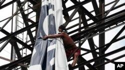 一名菲律宾工人把公路边的一个巨幅广告捆好,以防台风海燕来袭。(2013年11月6日)