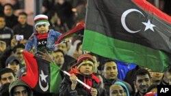 ປະຊາຊົນຊາວລີເບຍພ້ອມກັບທຸງຊາດໃນສະໄໝເປັນລາຊະອານາຈັກ ໂຮມຊຸມນຸມສະເຫຼີມສະຫຼອງວັນຄົບຮອບປີ ທຳອິດ ແຫ່ງການປະຕິວັດ ຄືວັນທີ 17 ກຸມພາ ທີ່ເມືອງ Benghazi ໃນພາກຕາເວັນອອກຂອງປະເທດ.