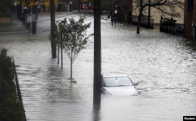 Floodwaters surround a car parked on a street in Hoboken, New Jersey, October 30, 2012, after Sandy, one of the biggest storms ever to hit the United States, roared ashore with fierce winds and heavy rain near Atlantic City.