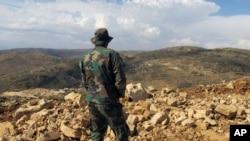 Hizbullah döyüşçüsü Livan sərhəddində yerləşən Brital kəndindən Suriyanı seyr edərkən.