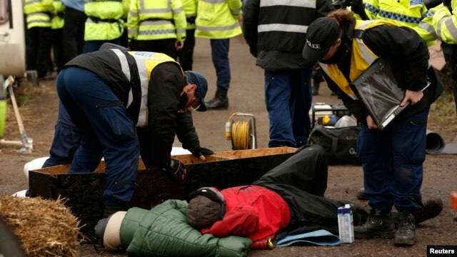 Police officers work to remove protesters who had chained themselves to a homemade coffin close to the entrance of the IGas exploratory gas drilling site at Barton Moss, near Manchester, northern England, March 6, 2014