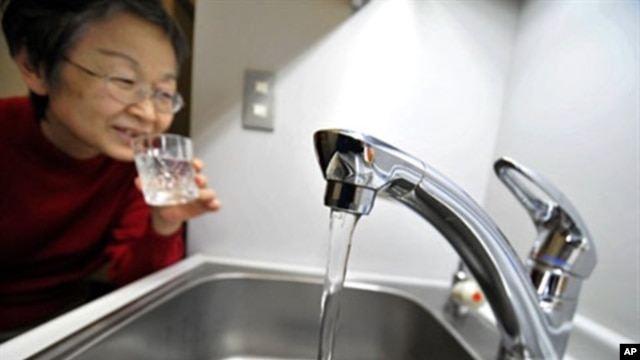 A woman fills a glass with water from a tap in Tokyo on March 23, 2011
