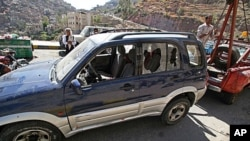 A damaged vehicle purported to belong to an American teacher shot by gunmen is towed away in Taiz, Yemen, Sunday, March 18, 2012.