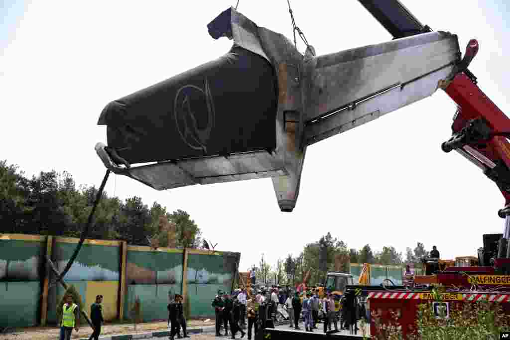 A firefighting crane lifts the tail section of a passenger plane which crashed near the capital Tehran, Iran, Aug. 10, 2014.