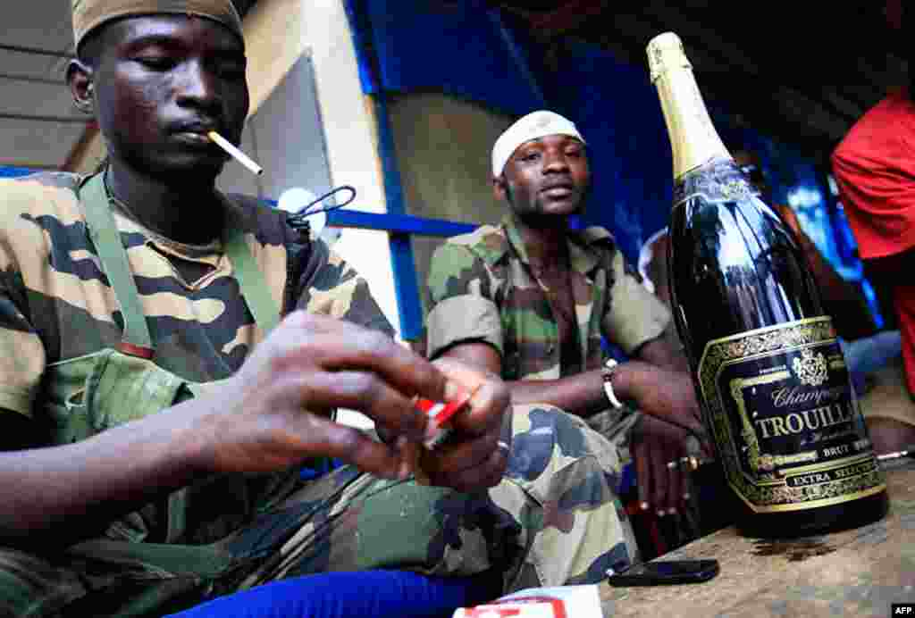 April 12: Republican forces soldiers in Ivory Coast relax around a bottle of champagne taken from the presidential residence. (AP Photo/Rebecca Blackwell)