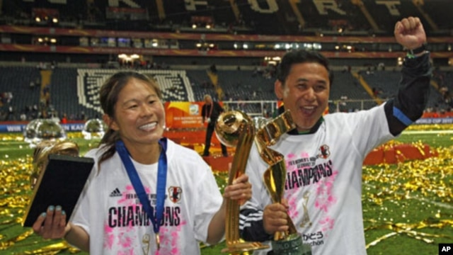 Japan's Homare Sawa (L) and head coach Norio Sasaki and pose with trophies after the end of their Women's World Cup final soccer match against the U.S. in Frankfurt, July 17, 2011