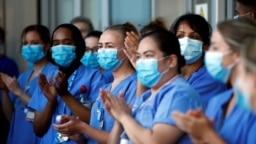 """Para petugas kesehatan Inggris (NHS) yang bertugas di Rumah Sakit Royal London Hospital serentak bertepuk tangan saat hari terakhir dari kampanye """"Clap for our Carers"""" untuk mendukung NHS di tengah pandemi COVID-19 pada 28 Mei 2020. (Foto: Reuters/Henry Nicholls)"""