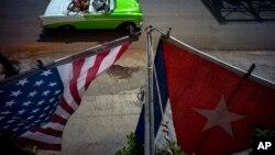 在古巴哈瓦那的舊城區一座樓房掛起的美國和古巴國旗。