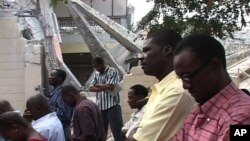 Catholics in Haiti attend mass outside after their church was heavily damaged in the recent earthquake.