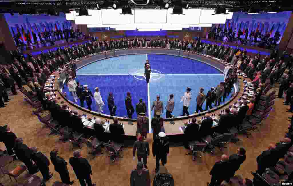 Leaders watch a ceremony honoring NATO military personnel for their service.(Reuters)