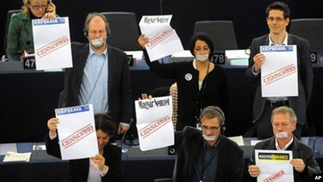 Parliament members protest as Hungary's Prime Minister Viktor Orban, unseen, delivers his speech at the European Parliament in Strasbourg, eastern France, 19 Jan. 2011