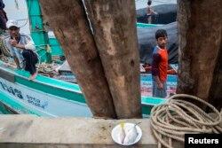 Ngư dân từ Myanmar làm việc trên một chiếc thuyền sau khi đánh cá trở về Ban Nam Khem, Thái Lan, ngày 14/12/2015.
