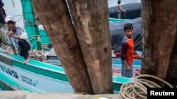 资料图片:来自缅甸的渔民在泰国渔船上工作