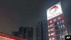 Một nhân viên cập nhật giá nhiên liệu sau nửa đêm tại 1 trạm xăng ở Vũ Hán, tỉnh Hồ Bắc, Trung Quốc, 20/3/2012