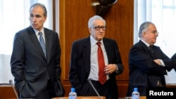 Lakhdar Brahimi (C), the U.N. envoy on Syria, waits with other delegates before a meeting at the United Nations European headquarters in Geneva, Switzerland, Dec. 20, 2013.