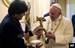 Pope Francis is presented with a gift of a crucifix carved into a wooden hammer and sickle, the Communist symbol uniting labor and peasants, by Bolivian President Evo Morales in La Paz, Bolivia, Wednesday, July 8, 2015.