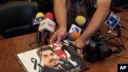A member of the media displays an image of slain Mexican journalist Edgar Daniel Esqueda Castro, in protest, before the start of a press conference in San Luis Potosi, Mexico, Oct. 6, 2017. The body of Esqueda Castro, a freelance photographer, was found one day after armed men wearing uniforms abducted him from his home.
