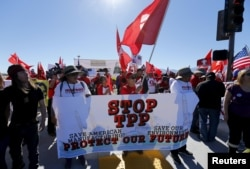 FILE - Protesters line one side of a roadway leading to Sunnylands where U.S. President Obama prepares to host leaders from Southeast Asia at the ASEAN Summit in Rancho Mirage, California, Feb. 15, 2016.