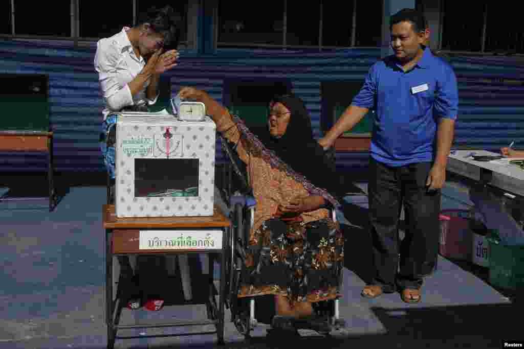 An election official greets a woman in a wheelchair as she casts her ballot at a polling station in Bangkok, March 30, 2014.