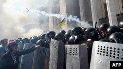 Một người biểu tình giữ lá chắn của sĩ quan cảnh sát tại phía trước tòa nhà quốc hội ở Kiev ngày 31/8/2015.