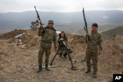 FILE - Armenian soldiers pose near a frontline in Nagorno-Karabakh, Azerbaijan, April 6, 2016.