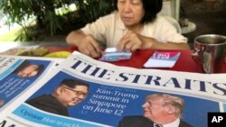 A news vendor counts her money near a stack of newspapers with a photo of U.S. President Donald Trump, right, and North Korea's leader Kim Jong Un on its front page on Friday, May 11, 2018, in Singapore.