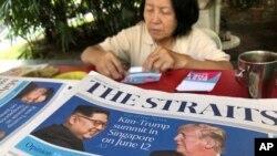 Một người bán báo đếm tiền bên cạnh một chồng báo có đăng ảnh TT Mỹ Donald Trump, phải, và lãnh tụ Triều Tiên Kim Jong Un trên trang nhất hôm 11/5/2018. (AP Photo/Wong Maye-E)