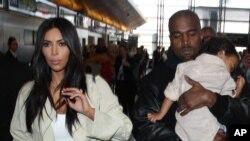 Kim Kardashian bersama Kanye West dan putri mereka North di bandara LAX di Los Angeles, AS, April lalu.