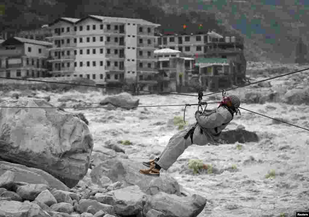 A man is pulled across to safety on a rope during a rescue operation in Govindghat in the Himalayan state of Uttarakhand as damaged buildings and the Alaknanda river are seen in the background. Flash floods and landslides unleashed by early monsoon rains have killed at least 560 people in Uttarakhand and left tens of thousands missing, officials said.