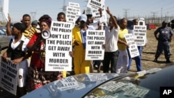 A group of protestors holds placards as a large crowd follows retired judge Ian Farlam and his team as they inspect the area where the bodies of mine workers were found after the shootings at Lonmin's platinum mine in Marikana near Rustenburg, South Africa, October 1, 2012.