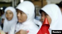Seorang aktivis Indonesia membagikan pita merah kepada pelajar di stasiun kereta Jakarta dalam kampanye memperingati Hari AIDS Sedunia 1 Desember 2006. (Foto: Reuters)