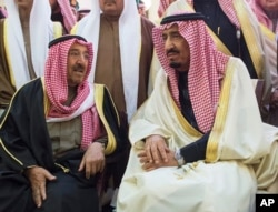 In this photo provided by Saudi Press Agency, newly enthroned King Salman, right, talks with Kuwait's emir, Sheikh Sabah Al-Ahmad Al-Jaber Al-Sabah, during King Abdullah's funeral in Riyadh, Jan. 23, 2015.